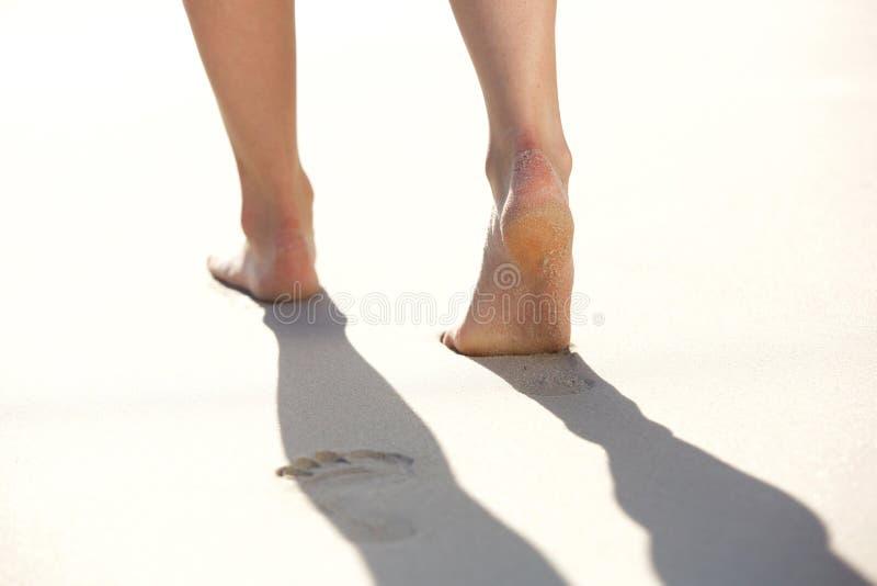 把脚印留在的妇女在海滩沙子 免版税库存照片