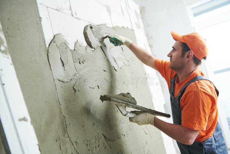 把膏药放的石膏工在墙壁上 慢的行动 免版税库存图片