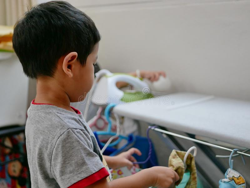 把被电烙的衬衣放的小亚裔婴孩在机架上 免版税库存照片
