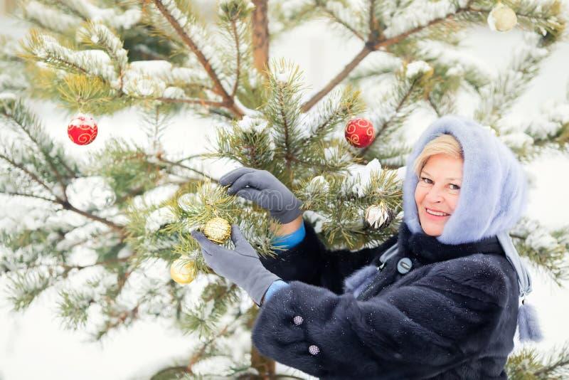把装饰品放的年长妇女在圣诞树上户外 免版税库存图片