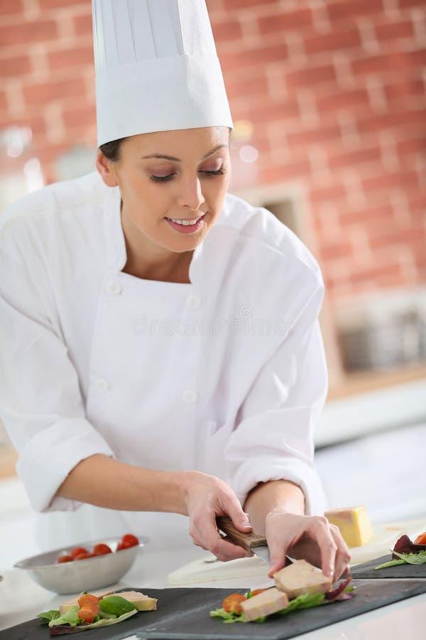把鹅肝放的年轻烹调厨师在板材上 库存照片