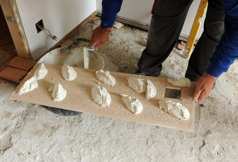把水泥灰浆放的瓦工在瓦片上 免版税图库摄影