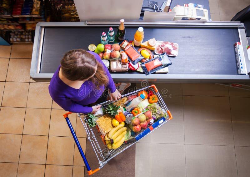 把从购物车的少妇物品放在结算离开的柜台上 免版税库存照片
