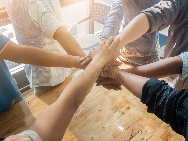 把他们的手放的人在木背景上在办公室 小组支持配合合作概念 免版税库存图片