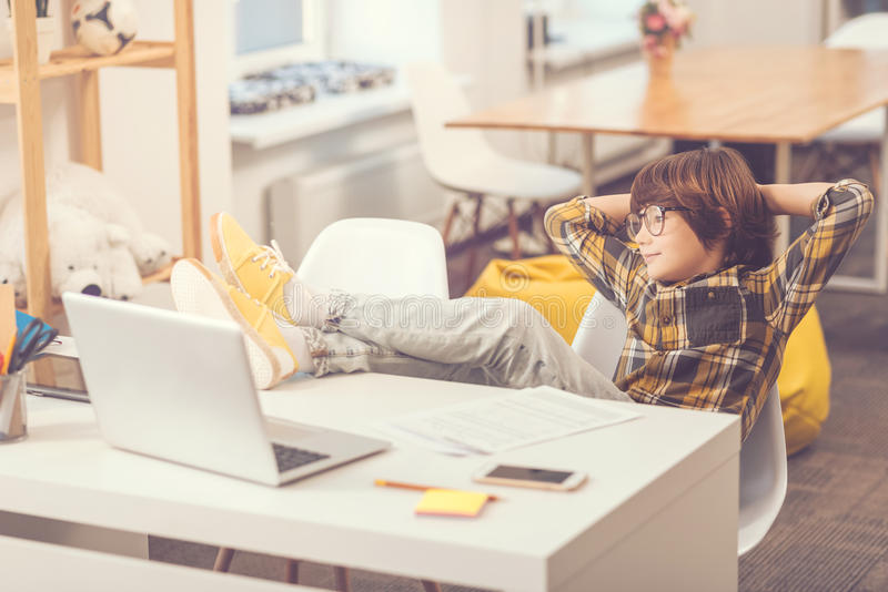 把他的腿放的确信的轻松的男孩在桌上 库存图片