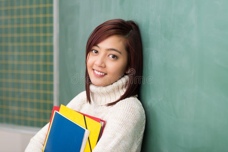 抓住她的文件的微笑的轻松的年轻学生 图库摄影