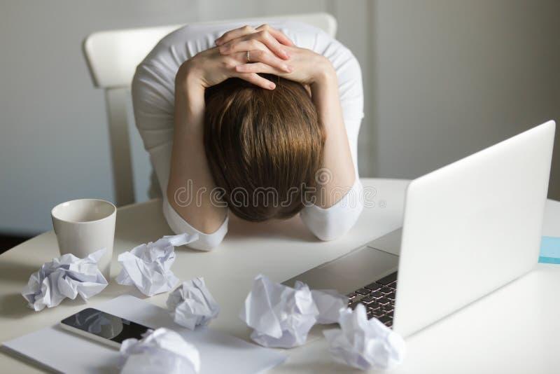 抓住她的头的妇女的画象在膝上型计算机附近 免版税库存照片