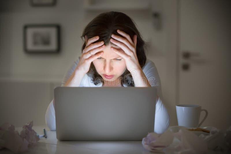 抓住她的头的妇女的画象在膝上型计算机附近 库存图片
