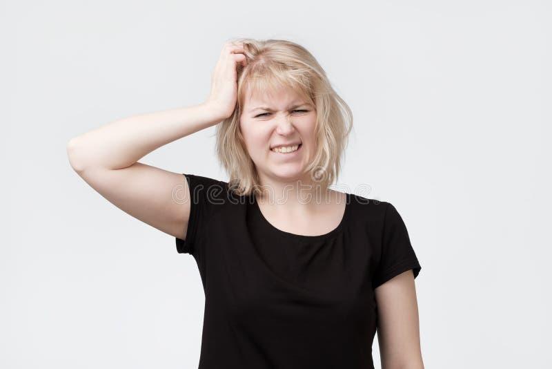抓头的美丽的年轻白肤金发的妇女 图库摄影