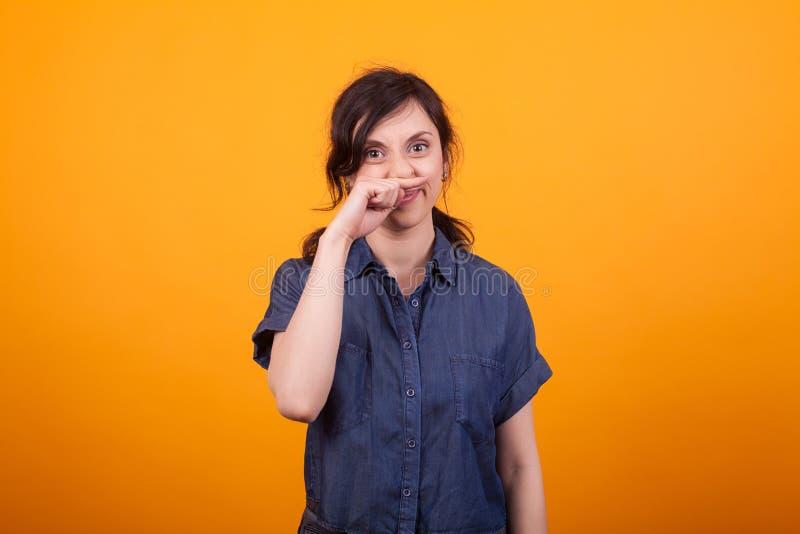 抓她的鼻子的滑稽的年轻女人画象在使用化妆用品以后 免版税库存照片