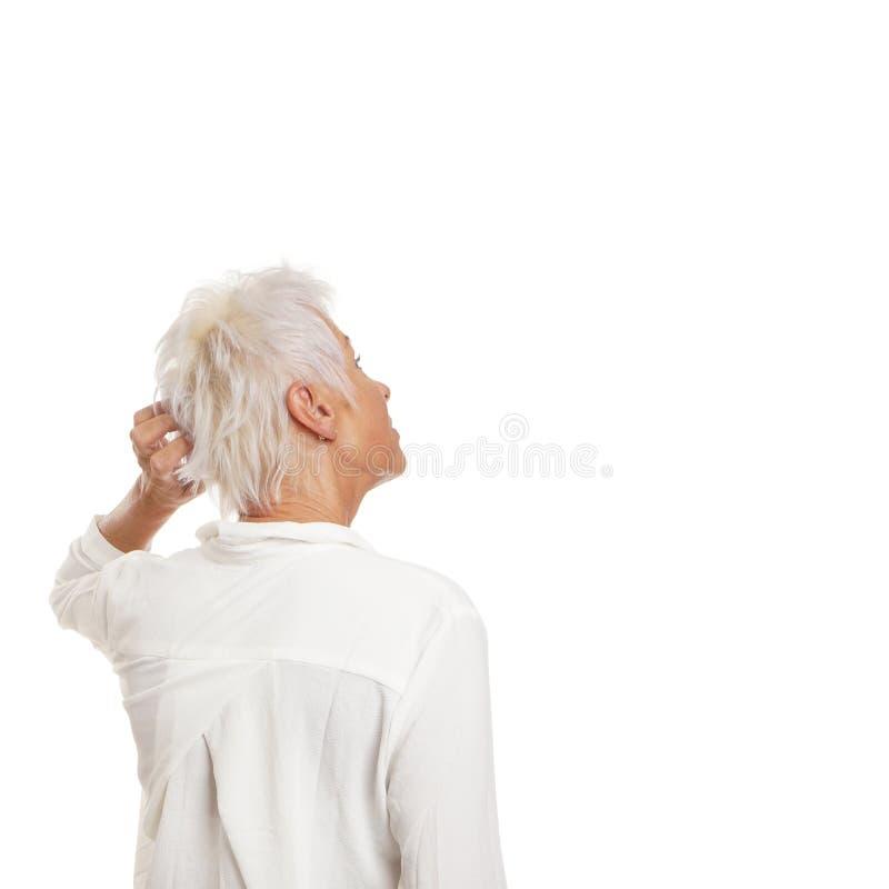 抓她的头的困惑的老妇人 库存照片