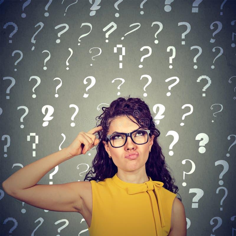 抓头的妇女寻求看许多问号的一种解决 免版税图库摄影