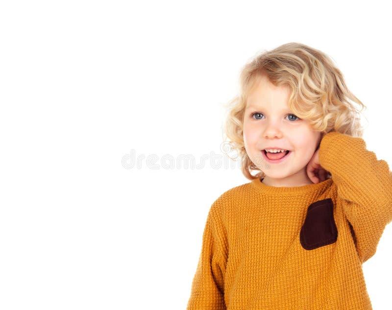 抓他的头的愉快的小男孩 免版税库存图片