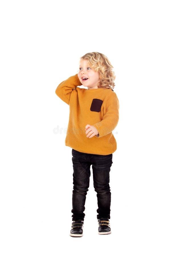 抓他的头的愉快的小男孩 免版税库存照片