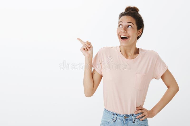 投下下颌的T恤杉和牛仔裤的热心被打动的和愉快的年轻快乐的妇女从喜悦和触目惊心指向 库存照片