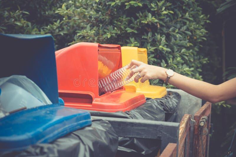 投下塑料瓶的年轻女人手入回收站 免版税图库摄影