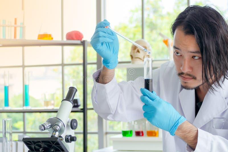 投下液体物质的亚裔科学家或化学家入试管,在实验室的医疗实验 免版税图库摄影