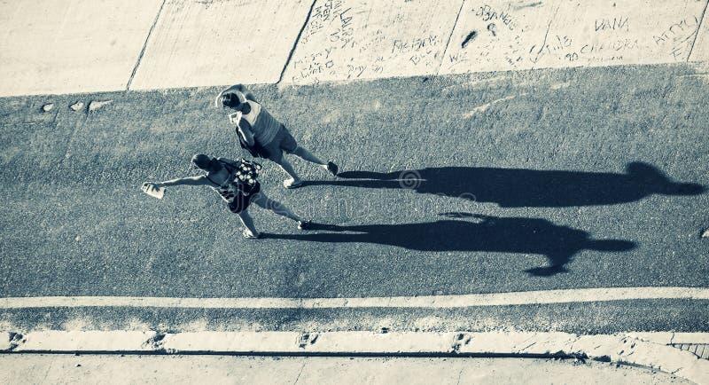投下长的阴影的剪影两名妇女的 图库摄影