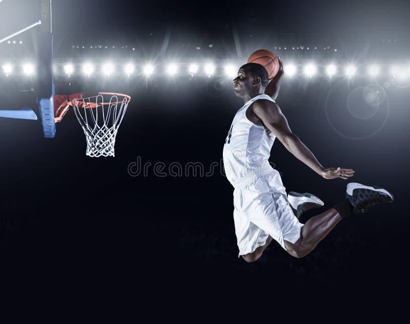 投中灌篮篮子的蓝球运动员 免版税图库摄影