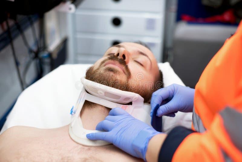 投入一个子宫颈衣领的紧急医生对患者在救护车 免版税库存照片