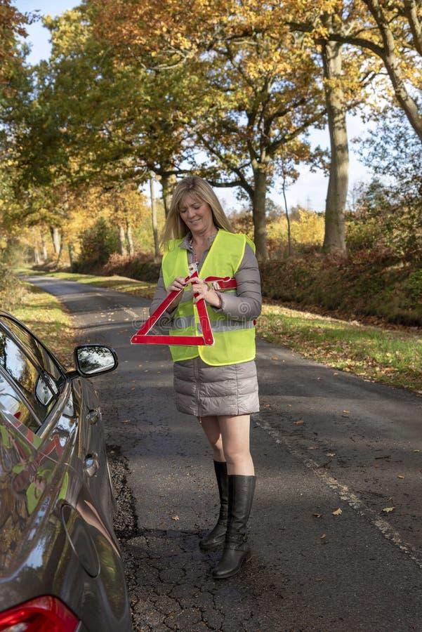 投入一个红色反射性安全三角的女驾车者 图库摄影