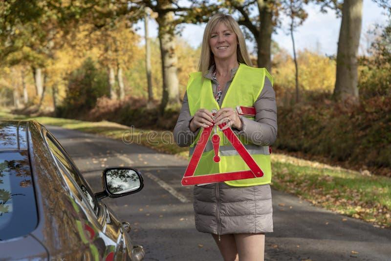 投入一个红色反射性安全三角的女驾车者 免版税图库摄影