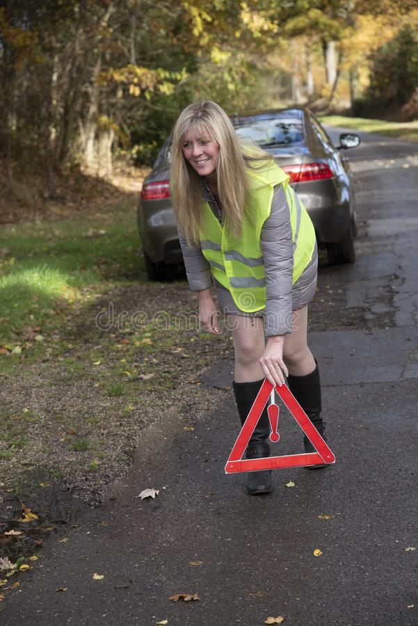 投入一个红色反射性安全三角的女驾车者 库存图片