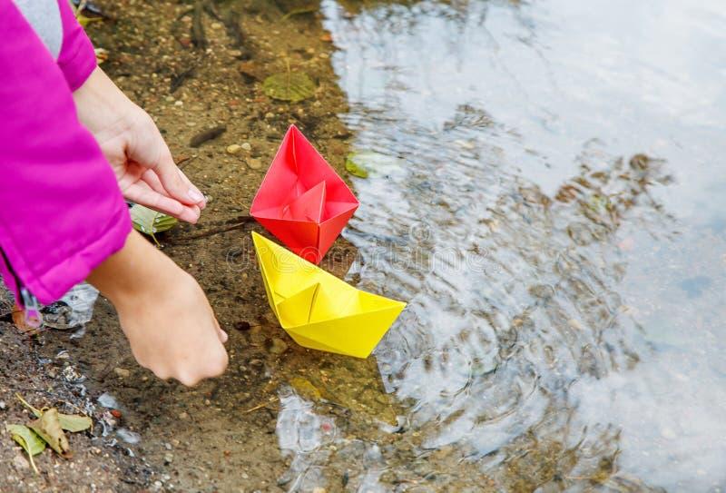 投入两条彩纸小船的女孩在小河 图库摄影