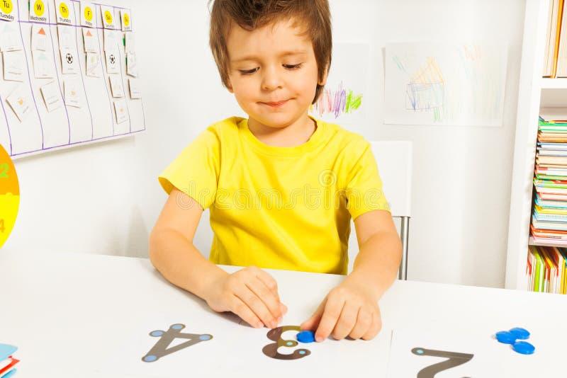 投入了硬币学会计数的微笑的男孩在数字 免版税库存图片