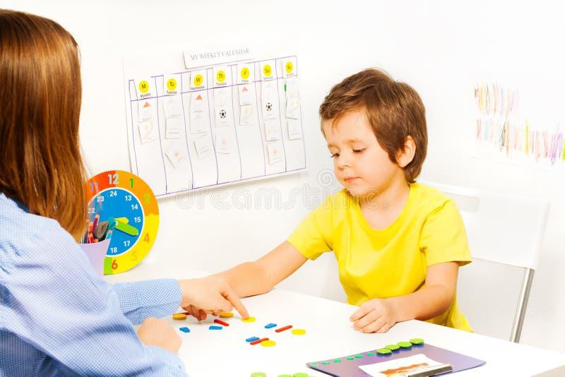 投入五颜六色的形状的硬币的男孩按顺序 免版税图库摄影