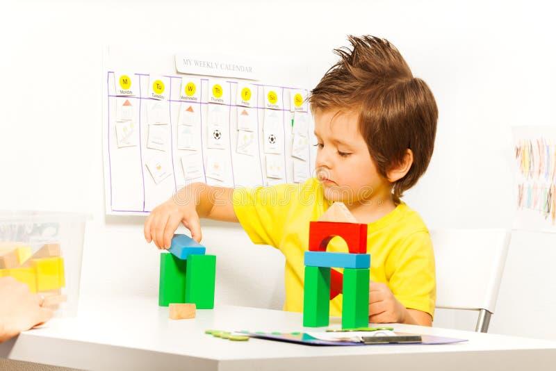 投入五颜六色的立方体的男孩在建筑比赛 免版税库存照片