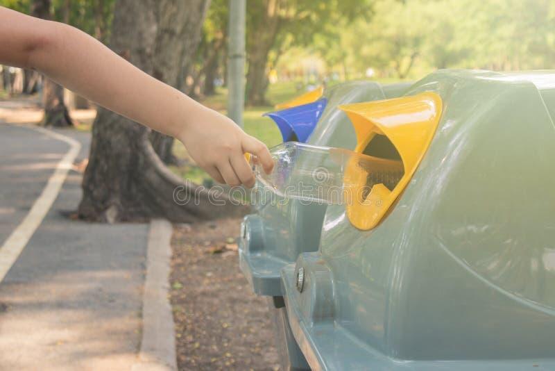 投入使用的塑料瓶的小孩手的关闭公开在公园回收站或被分离的废物箱 库存图片