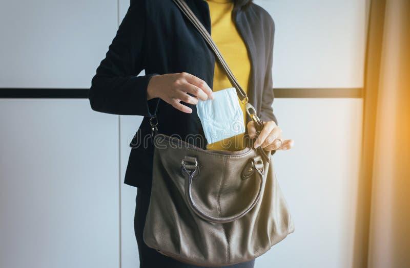 投入卫生棉的妇女手在提包,白色月经垫 免版税库存照片