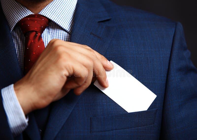 投入参观卡片的商人在口袋 免版税库存照片