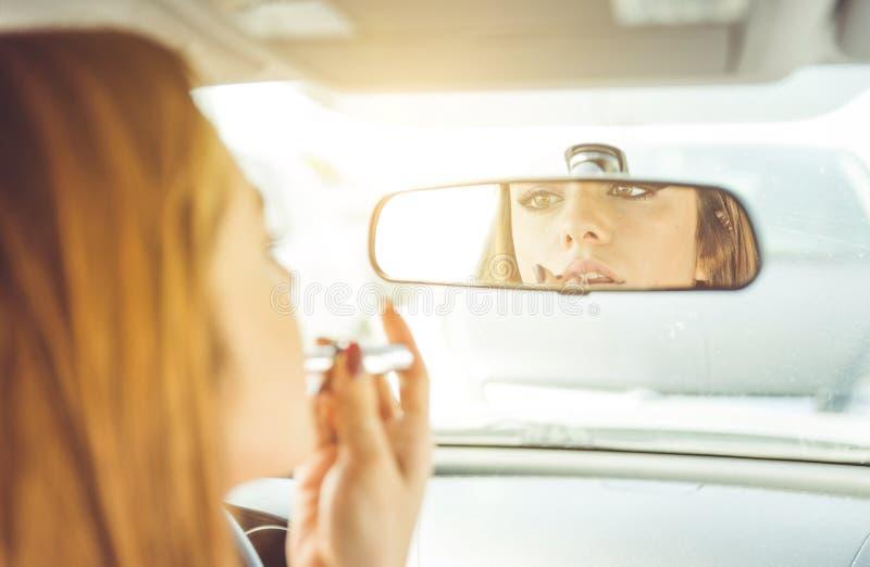 投入唇膏的妇女在汽车 免版税库存图片
