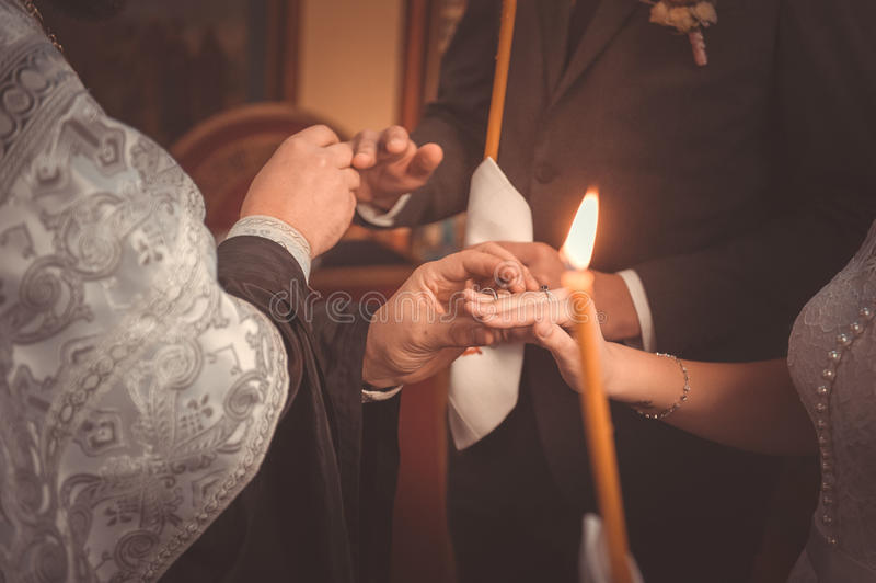 投入圆环的教士在正统婚礼期间 免版税库存图片