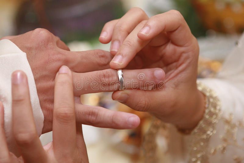 投入在一个圆环(婚礼乐队)在一个人 免版税库存图片