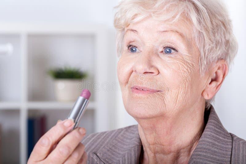 投入在唇膏的年长妇女 库存图片