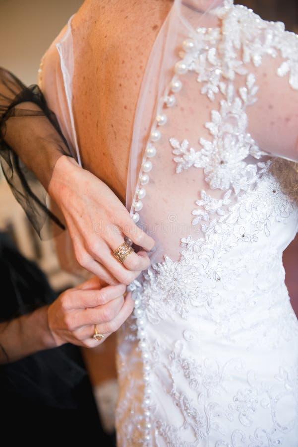 投入在婚纱 对扣紧礼服的按钮的新娘的帮手 免版税图库摄影