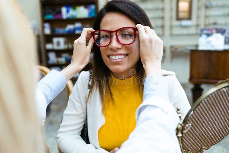 投入在微笑的美女的镜片的年轻眼科医生在视觉商店 免版税库存照片