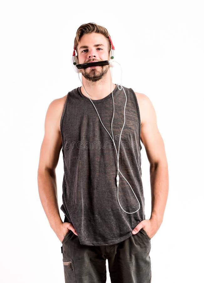 投入在耳机和逃命 不剃须的在耳机的人听的音乐 性感的肌肉人听体育音乐 ? 库存照片
