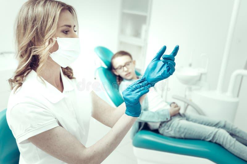 投入在蓝色手套的被集中的牙医 库存图片