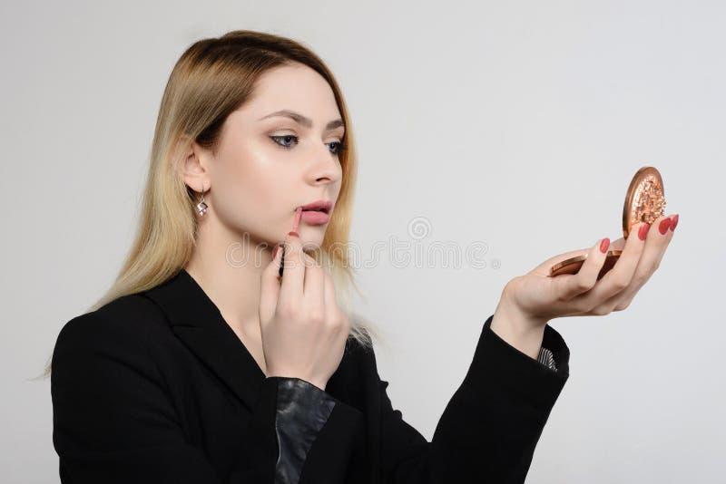 投入在镜子前面的嘴唇光泽的美丽的女孩 库存图片