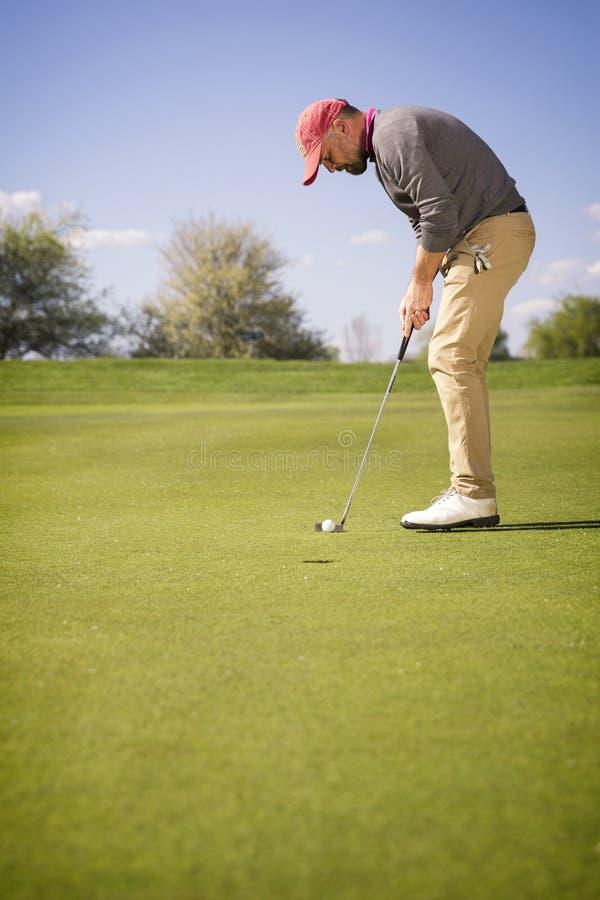 投入在绿色的男性高尔夫球运动员 免版税库存照片