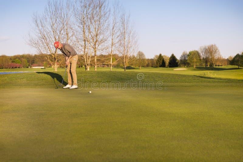 投入在绿色的高尔夫球运动员 图库摄影