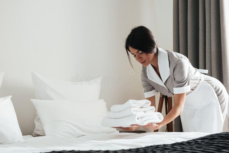 投入堆新鲜的白色毛巾的年轻旅馆佣人 库存图片