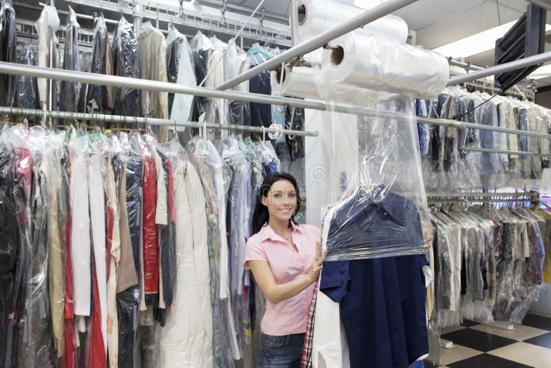 投入塑料的一名愉快的中间妇女的画象对干洗的衣裳在洗衣店 免版税库存照片