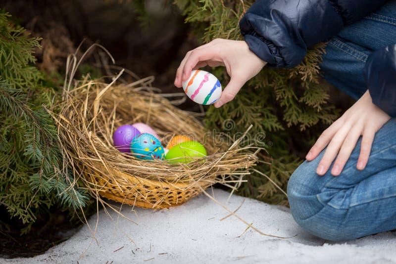 投入复活节彩蛋的小女孩在巢冷的多雪的天 免版税库存图片