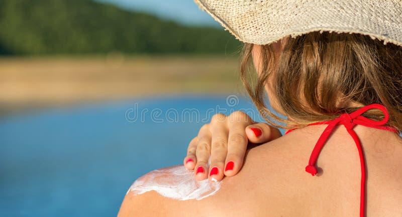 投入太阳化妆水的少妇在暑假 图库摄影