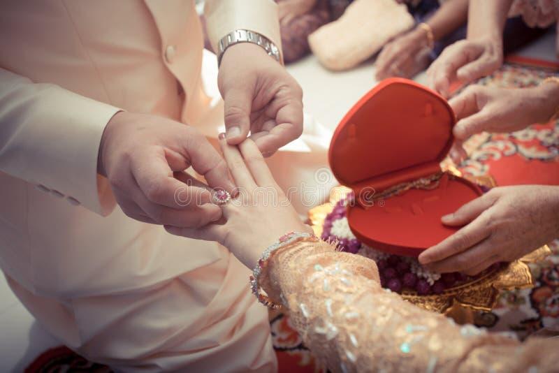 投入婚戒的泰国新郎 免版税库存照片